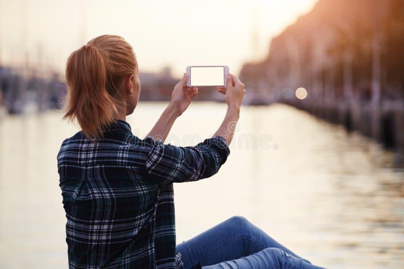 Tillbaka sikt av det kvinnliga turist- fotografera landskapet på mobiltelefonen, medan att tycka om hennes semester semestrar, arkivfoton