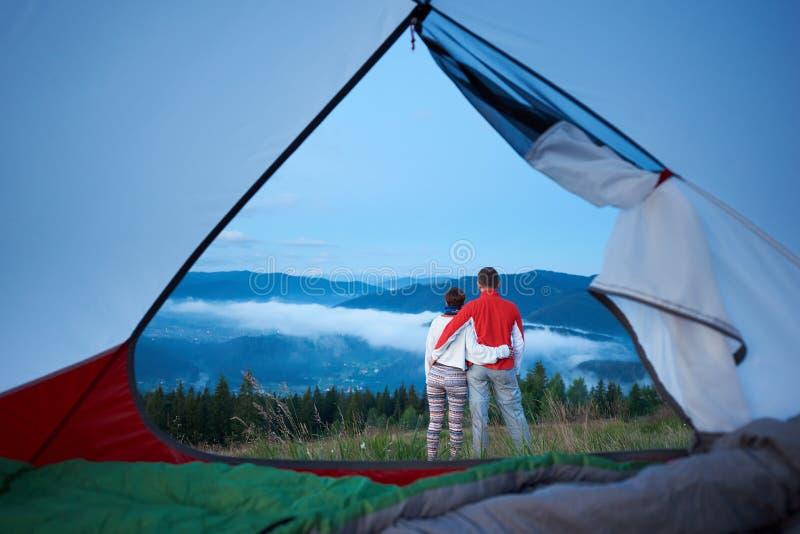 Tillbaka sikt av det söta paranseendet som kramar sig som beundrar sikten av berg fotografering för bildbyråer