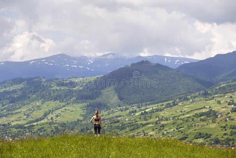 Tillbaka sikt av det slanka anseendet för ung kvinna på den gräs- dalen på bakgrund av gröna berg på solig sommardag arkivfoton