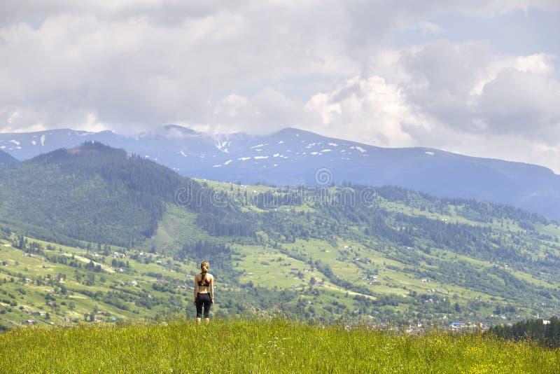 Tillbaka sikt av det slanka anseendet för ung kvinna på den gräs- dalen på bakgrund av gröna berg på solig sommardag arkivbild