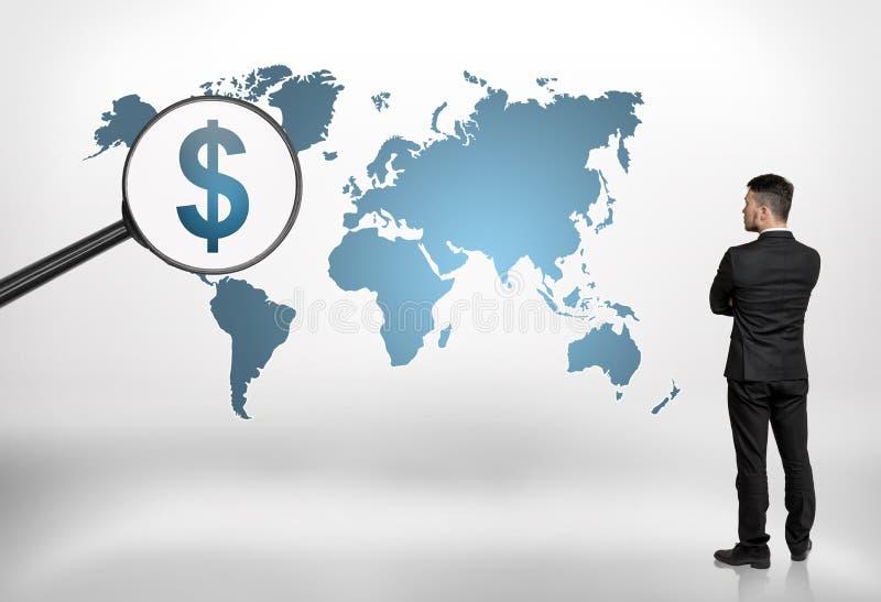 Tillbaka sikt av en affärsman som ser världskartan med det förstorande dollartecknet för stor förstoringsapparat på det arkivfoton