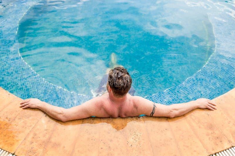 Tillbaka sikt av en Caucasian man som vilar i en simbassäng i en semesterort fotografering för bildbyråer