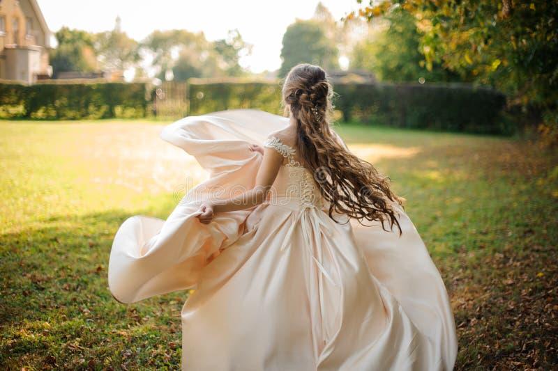 Tillbaka sikt av en härlig brud som rotera i en bröllopsklänningdans på det gröna fältet arkivbild
