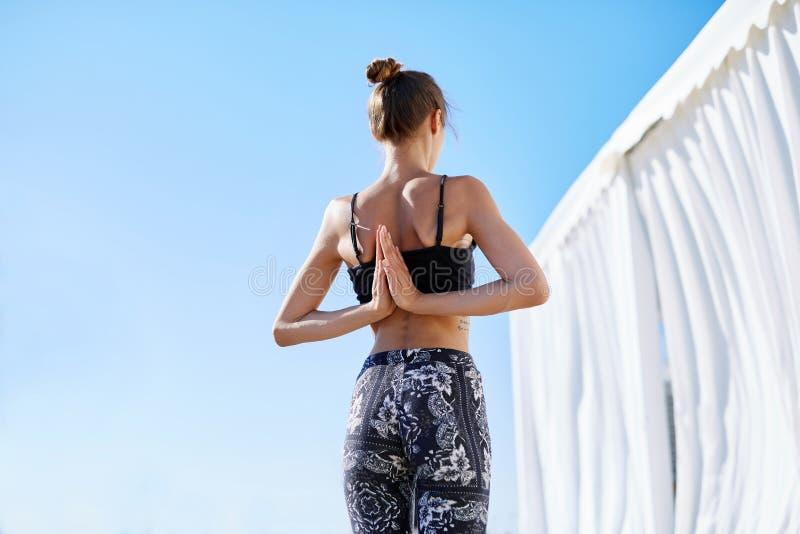 Tillbaka sikt av en härlig ung kvinna att göra yogaövningar på sjösidan mot blå himmel Mening så bekvämt och att koppla av royaltyfria foton