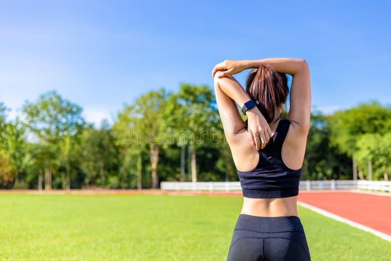 Tillbaka sikt av en härlig ung kvinna som sträcker under hennes övning i morgonen på ett rinnande spår, klar blå himmel med suddi royaltyfria foton