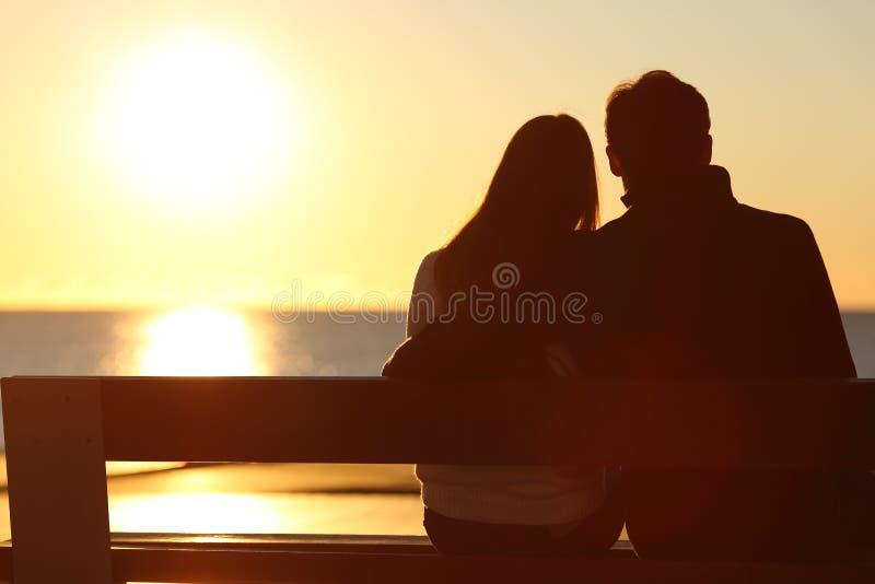 Tillbaka sikt av en hållande ögonen på sol för par på stranden arkivbilder