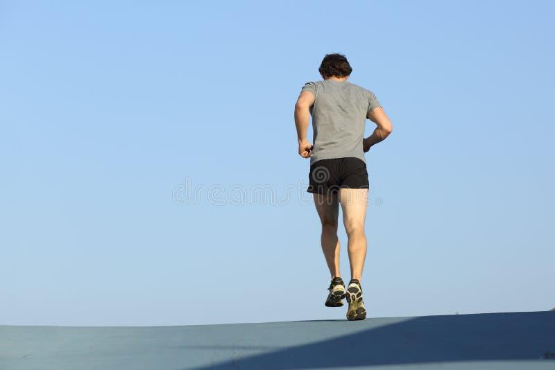 Tillbaka sikt av en joggermanspring mot blå himmel arkivbilder