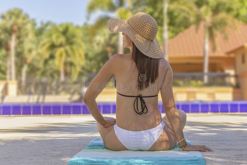 Tillbaka sikt av en kvinna som framme sitter i en bikini på en strandhandduk av pölen med en hatt som ser vänstersida arkivbilder