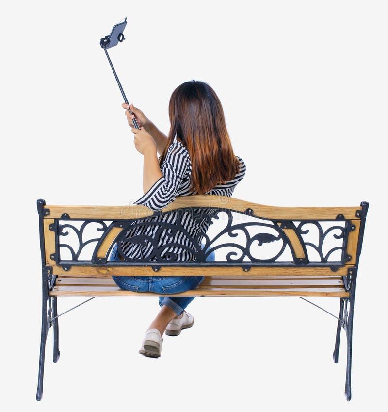Tillbaka sikt av en kvinna som gör selfie att klibba ståendesammanträde på bänken royaltyfri foto
