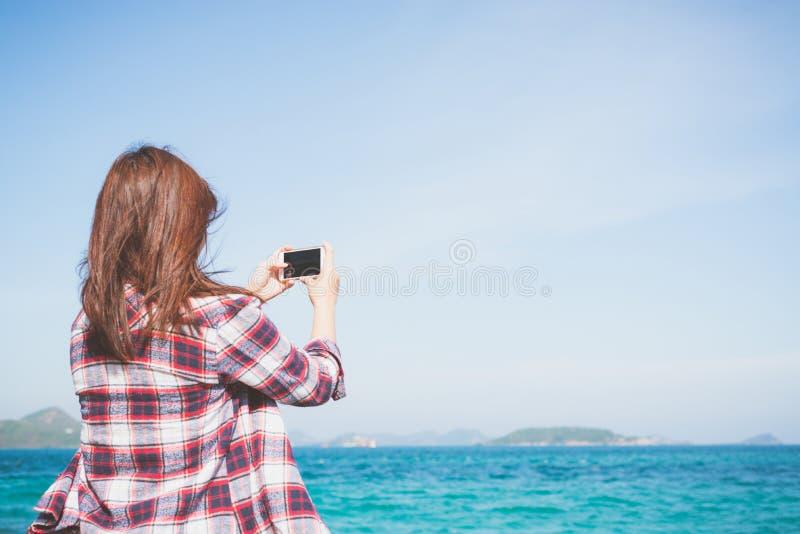 Tillbaka sikt av en kvinna som tar fotografiet med den smarta telefonkameran på horisonten på stranden royaltyfri foto