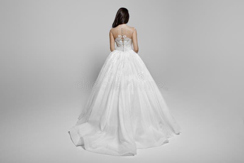 Tillbaka sikt av en kvinnlig modell f?r superbebrunett i en vit prinsessabr?llopskl?nning, p? en vit bakgrund arkivbilder