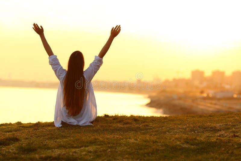 Tillbaka sikt av en lycklig kvinna som lyfter armar på solnedgången arkivfoto