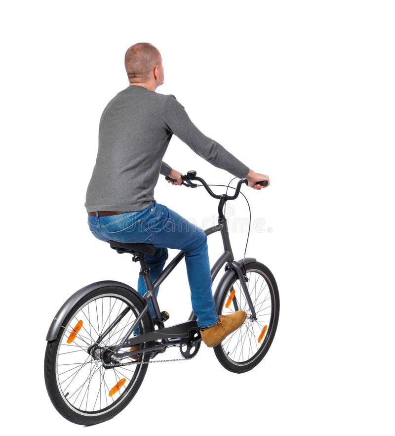 Tillbaka sikt av en man med en cykel royaltyfri foto