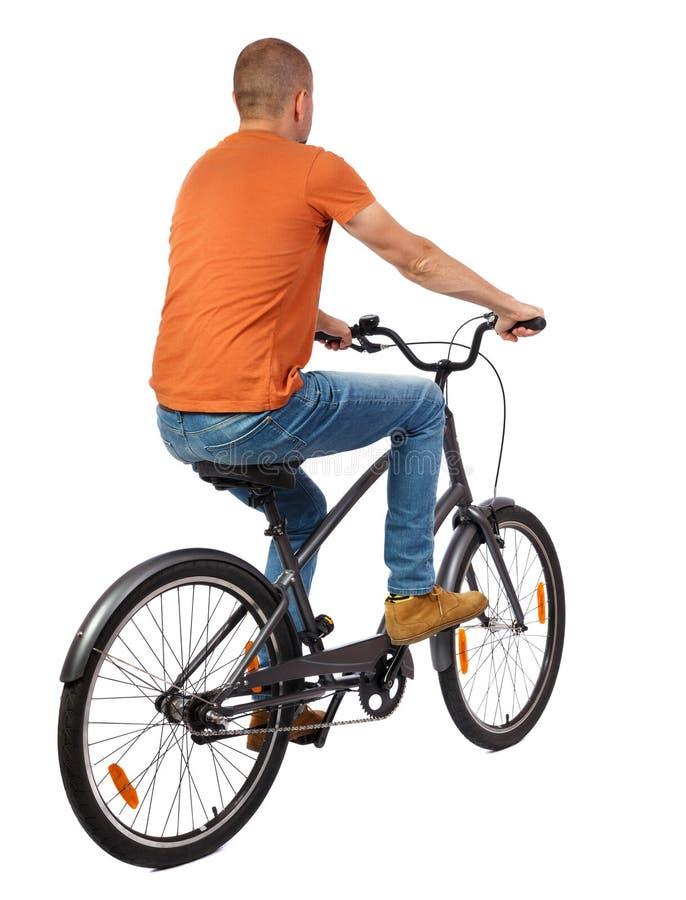 Tillbaka sikt av en man med en cykel royaltyfria foton
