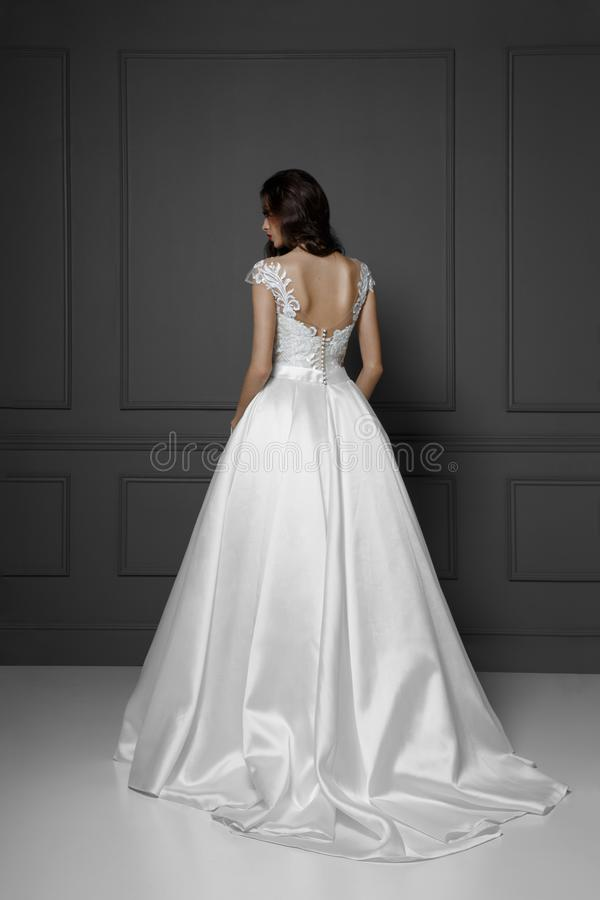 Tillbaka sikt av en mjuk brunettmodell i den vita delikata prinsessabr?llopskl?nningen som isoleras p? en gr? bakgrund royaltyfri bild