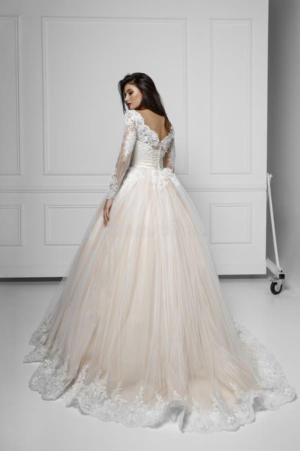 Tillbaka sikt av en modebrunettmodell i härlig lång bröllopsklänning, nära den vita väggen, skott i studion, kopieringsutrymme royaltyfria bilder