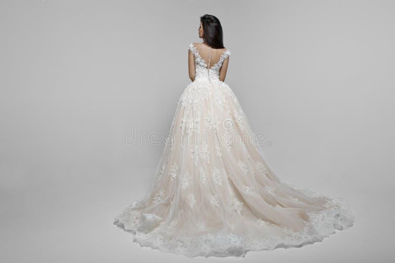 Tillbaka sikt av en sinnlig kvinnlig modell i lång wendding klänning som isoleras på en vit bakgrund arkivbild