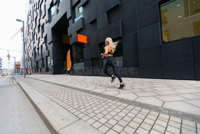 Tillbaka sikt av en snabb rinnande färdig kvinna i modern stadsmiljö royaltyfri bild