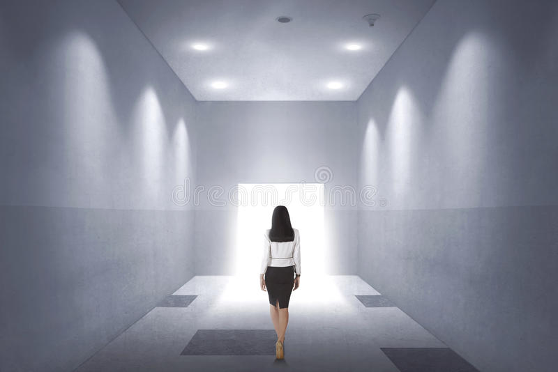 Tillbaka sikt av en ung asiatisk affärskvinna som går till den öppnade dörren royaltyfri bild