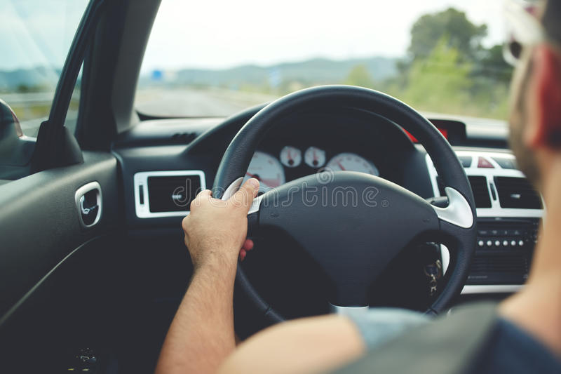 Tillbaka sikt av en ung man som kör hans bil under sommartur royaltyfri bild