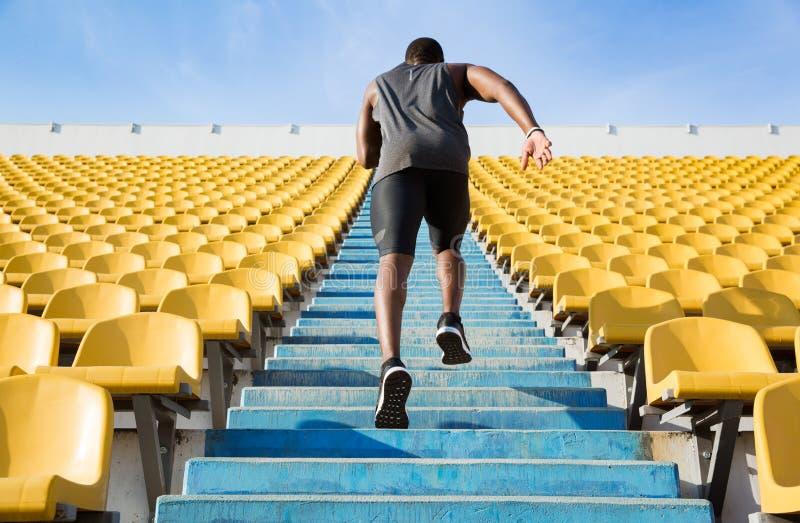 Tillbaka sikt av en ung man som uppför trappan kör fotografering för bildbyråer