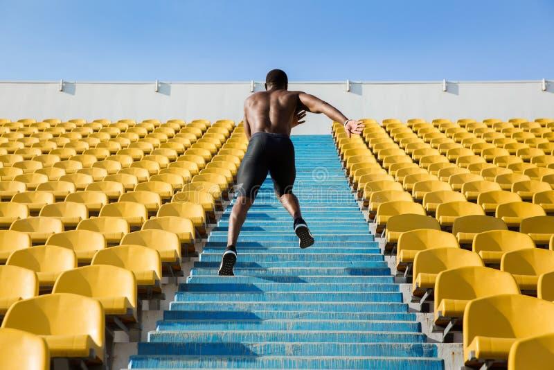 Tillbaka sikt av en ung man som uppför trappan kör royaltyfri foto