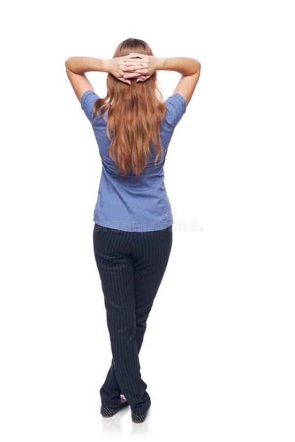 Tillbaka sikt av ett kvinnaanseende med över huvudet händer arkivfoton