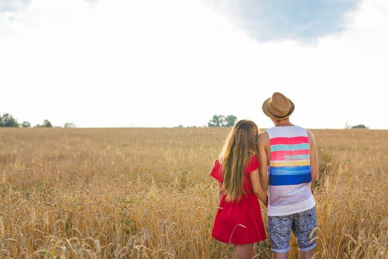 Tillbaka sikt av ett par som rymmer sig och beskådar landskap, medan föreställa deras framtid fotografering för bildbyråer