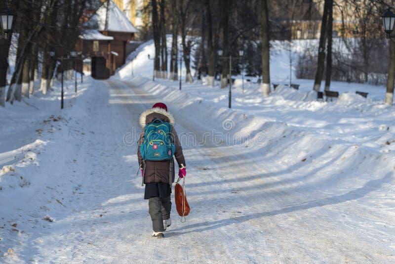 Tillbaka sikt av flickan med ryggsäcken royaltyfria bilder