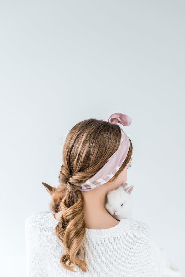 Tillbaka sikt av flickan som rymmer förtjusande päls- kaniner royaltyfri fotografi