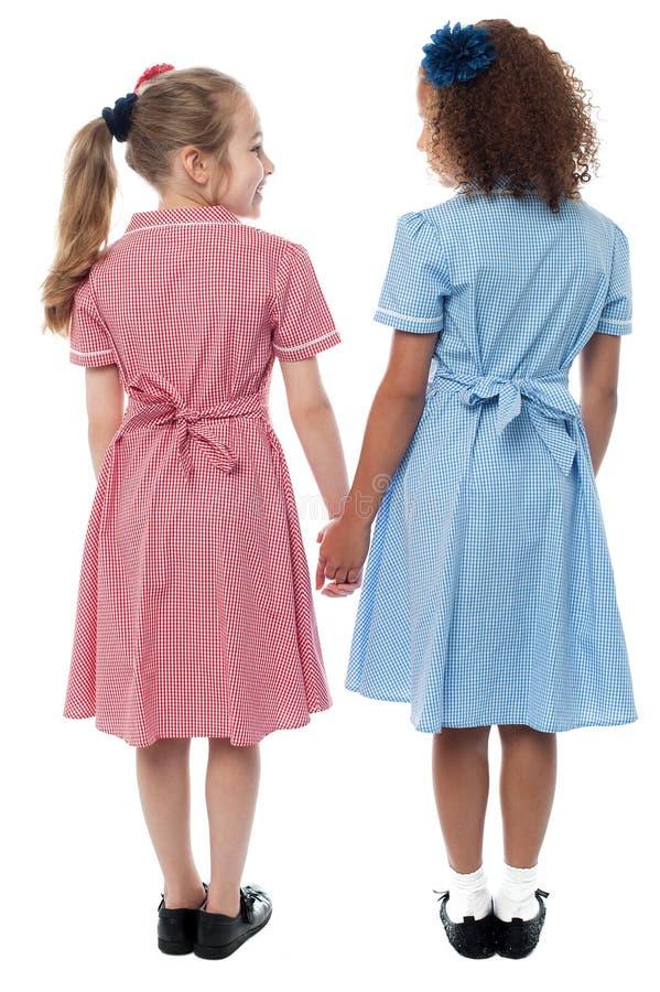 Tillbaka sikt av flickor i skolalikformig arkivbild