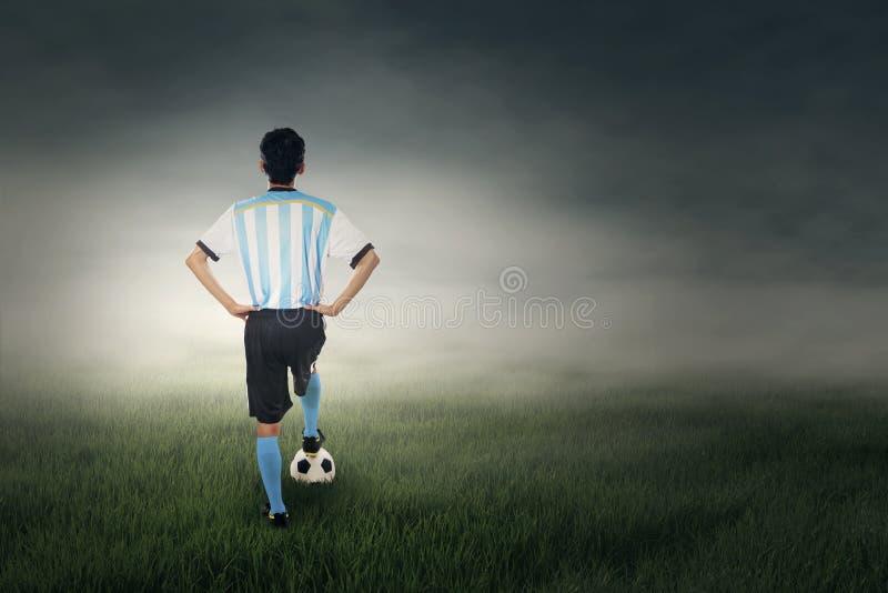 Tillbaka sikt av fotbollspelaren på fältet arkivbilder