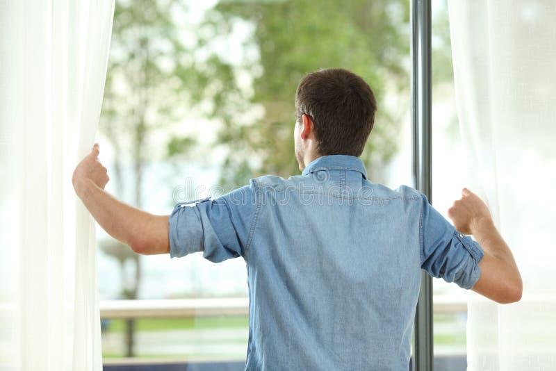 Tillbaka sikt av gardiner och att se för manöppning bort royaltyfri bild