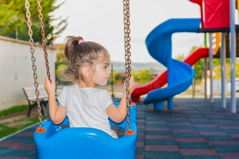 Tillbaka sikt av gulligt svänga för liten flicka arkivfoto