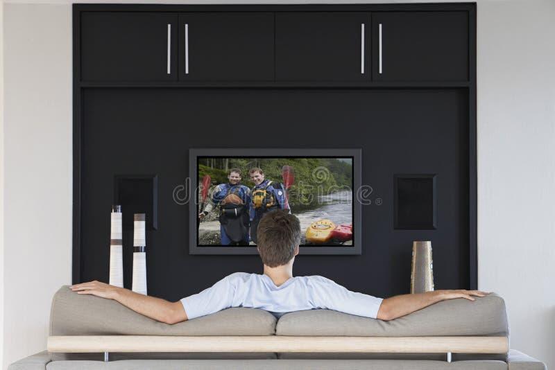 Tillbaka sikt av hållande ögonen på television för mitt--vuxen människa man i vardagsrum fotografering för bildbyråer