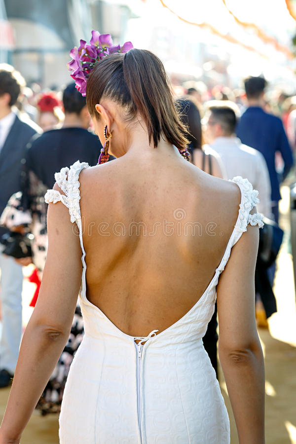 Tillbaka sikt av klänningen för flamenco för härlig modekvinna den bärande Spansk folklore Seville April Fair arkivfoto