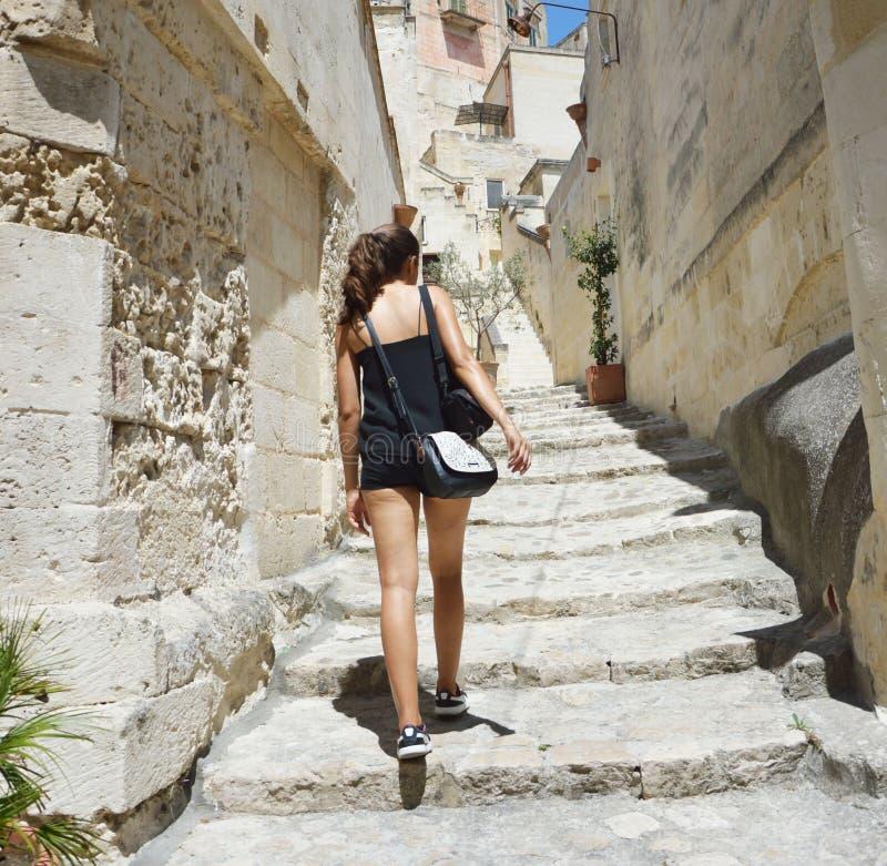 Tillbaka sikt av klättringen för ung kvinna in till den gamla staden av Matera Attraktivt handelsresandeflickabesök Sassi di Mate arkivfoton