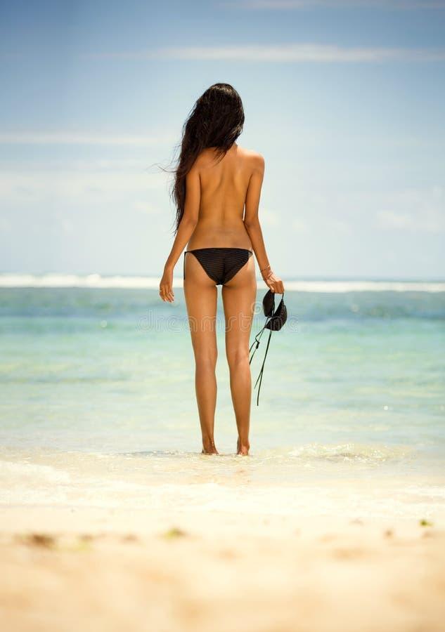 Tillbaka sikt av kvinnan i topless arkivfoton