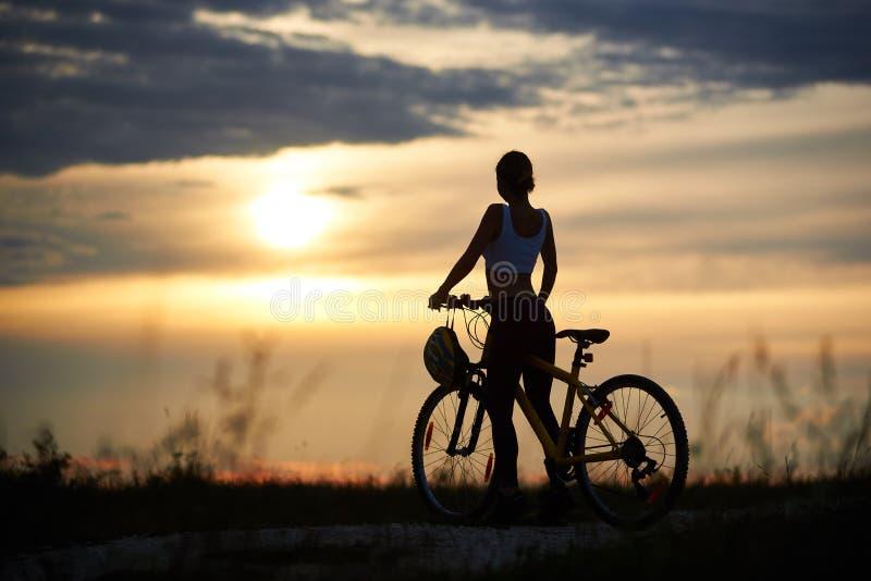 Tillbaka sikt av kvinnan med cykelanseende på vägen bland gräs som tycker om solnedgången på aftonhimmel arkivfoton
