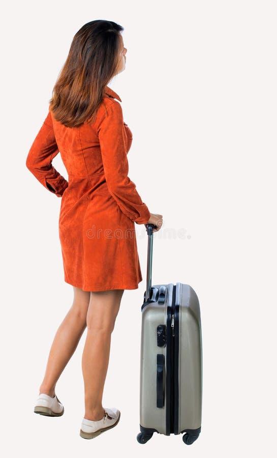 Tillbaka sikt av kvinnan med resväskan som ser upp arkivbild