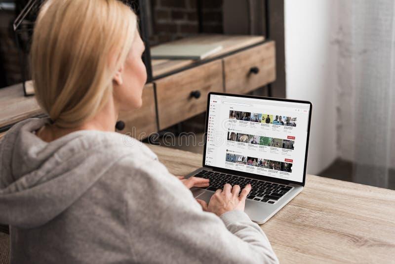 tillbaka sikt av kvinnan som använder bärbara datorn med den youtube websiten royaltyfria foton