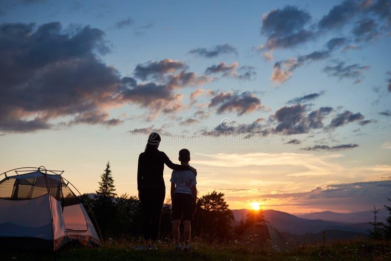 Tillbaka sikt av kvinnan som kramar near campa för barn i berg på gryninganseendet på gräs med vildblommor royaltyfria bilder