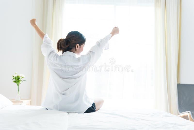 Tillbaka sikt av kvinnan som sträcker i morgon, når att ha vaknat upp på säng arkivbilder