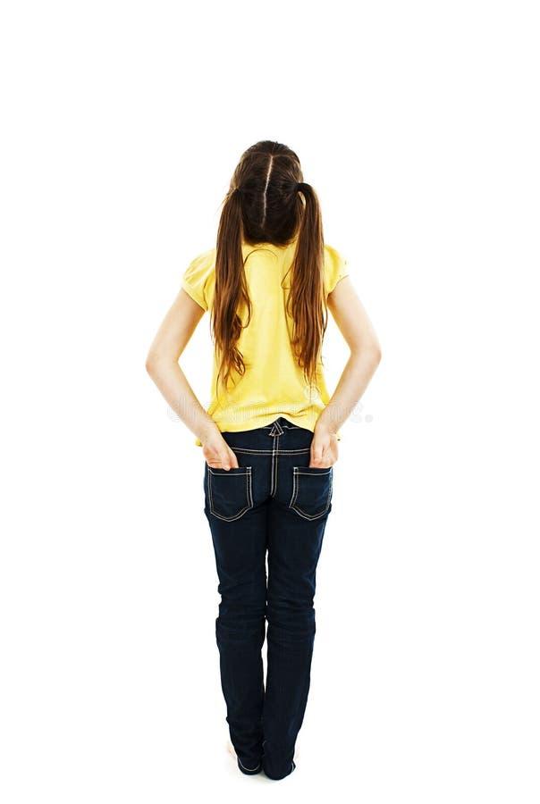 Tillbaka sikt av lilla flickan med båda händer i hennes fack som ser upp på väggen arkivfoto