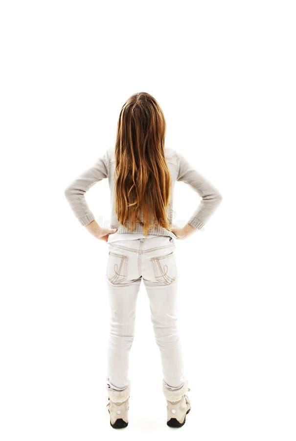 Tillbaka sikt av lilla flickan som ser väggen. Bakre sikt arkivbilder