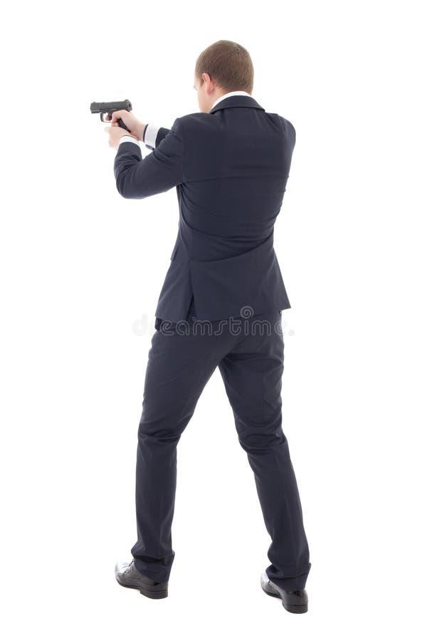 Tillbaka sikt av mannen för specialt medel i affärsdräkten som poserar med vapnet royaltyfria bilder