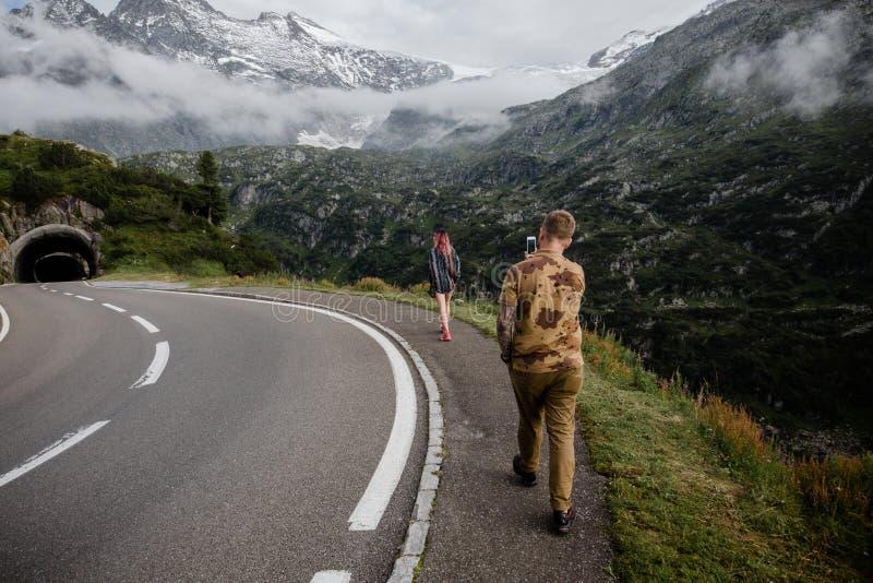 tillbaka sikt av mannen med smartphonen som fotograferar den unga kvinnan som går på vägen nära bergtunnelen arkivfoto