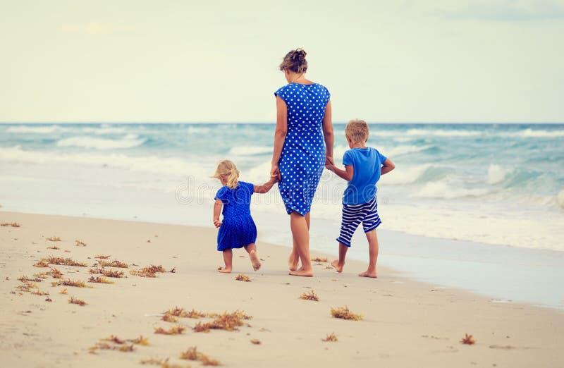 Tillbaka sikt av modern och två ungar som går på stranden arkivbilder
