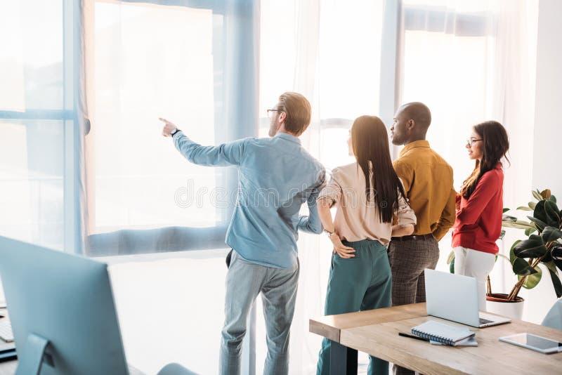 tillbaka sikt av multietniska affärskollegor som ut ser fönstret fotografering för bildbyråer