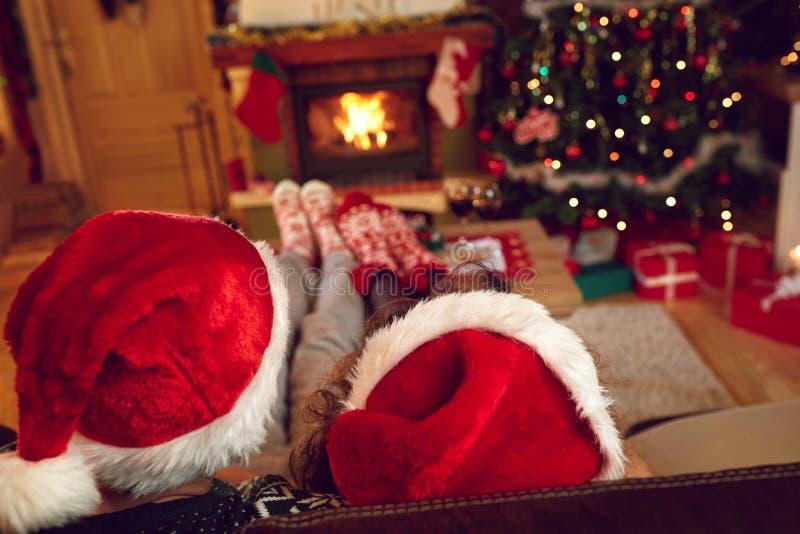 Tillbaka sikt av par med Santa Claus hattar arkivfoton